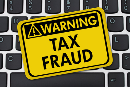 Online Tax Fraud, Computer Keyboard with a yellow warning sign with text Tax Fraud
