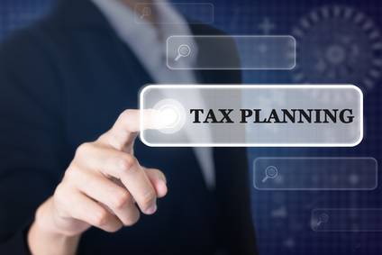 Businessman pressing a TAX PLANNING concept button. Can be used in advertising.